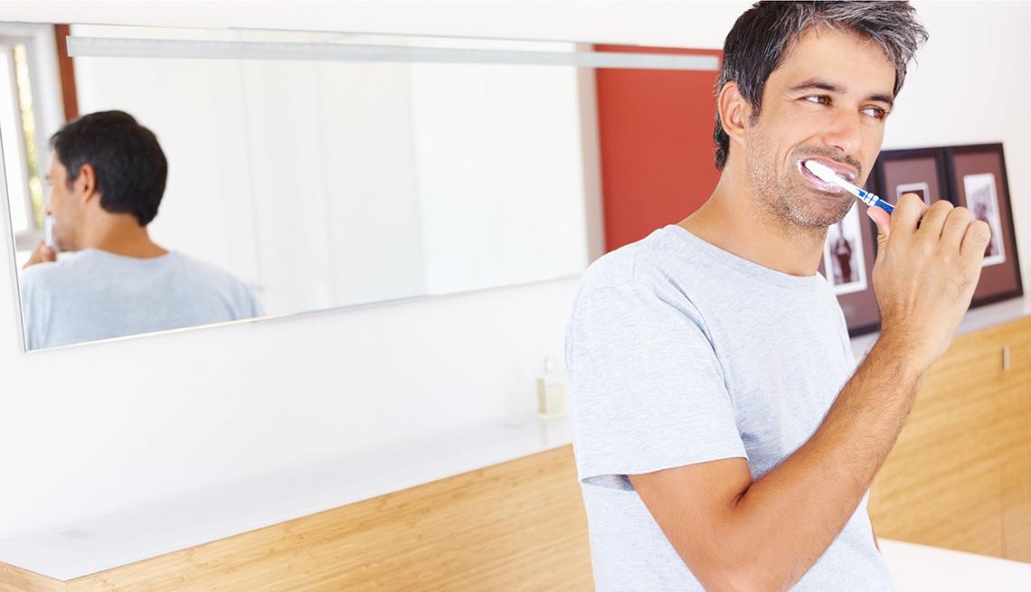 Mature man brushing his teeth to avoid cavities